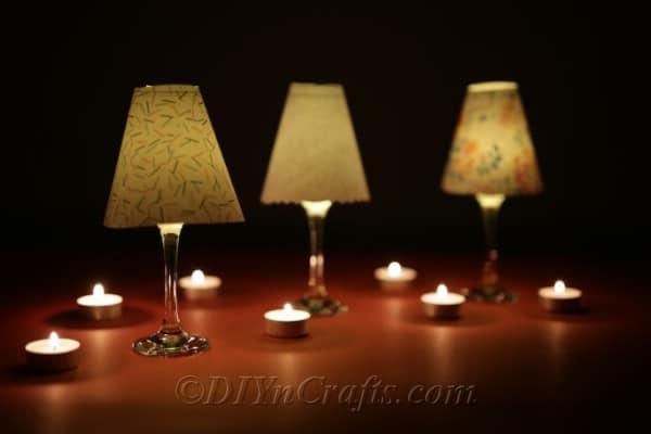 Lit up wine glass lanterns shown in the dark.