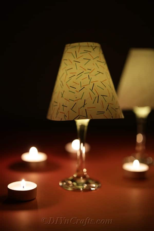 A completed wine glass lantern sitting on a table in the dark to showcase the glow of candle light