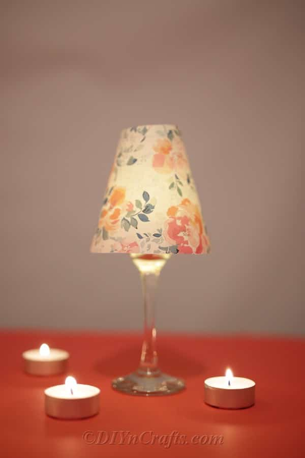 A completed diy wine glass lantern sitting on an oraneg surface with candle lit inside the glass