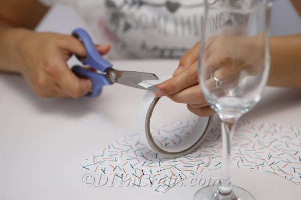 Attaching the two ends of the craft paper together to make a paper shade for the diy wine glass lantern tealight candle holders