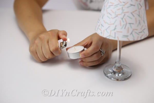 A woman lighting a tealight candle to place inside the diy wine glass lantern