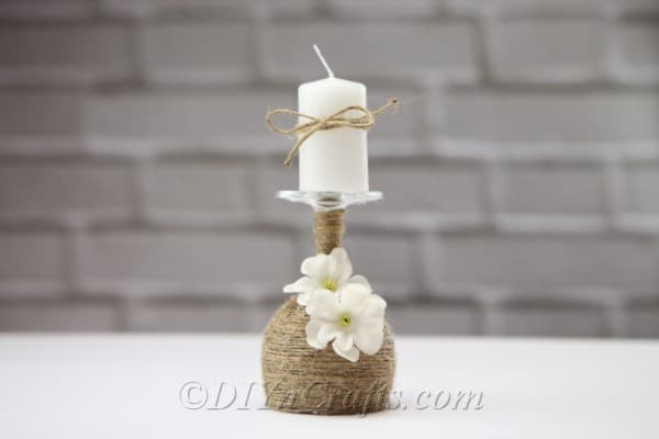 A rustic candle holder made from a wine glass with a candle on top.