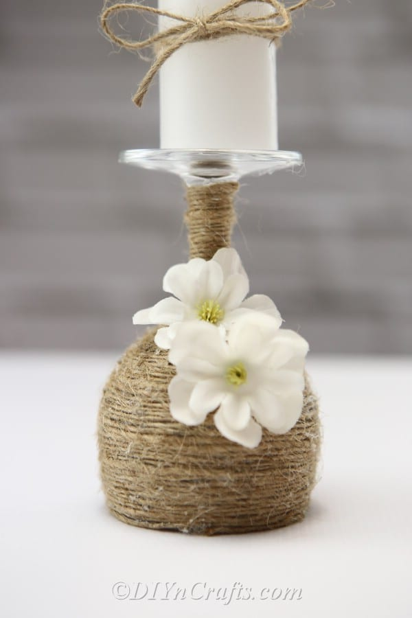 A close-up of a rustic candle holder made from a wine glass with a focus on the faux flowers.