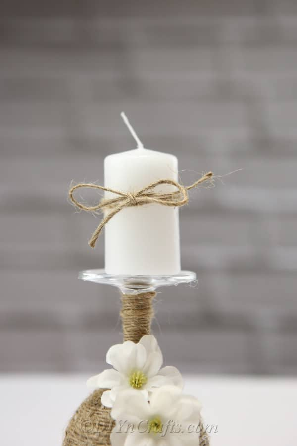 A close-up of a rustic candle holder made from a wine glass with a focus on the candle.