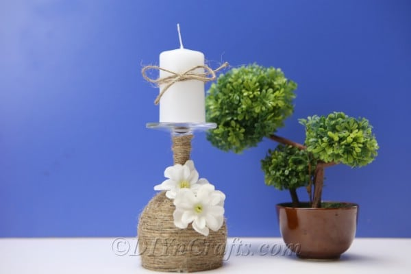 A rustic candle holder is displayed next to a plant with a blue backdrop.