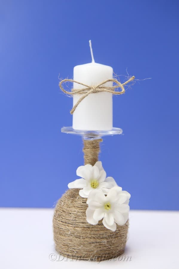 A rustic candle holder made from a wine glass with a candle on top and a blue wall in the backdrop.