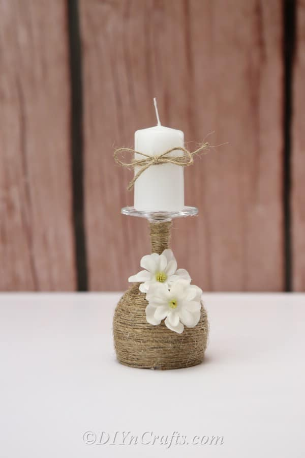 A rustic candle holder is displayed with a fence in the background.