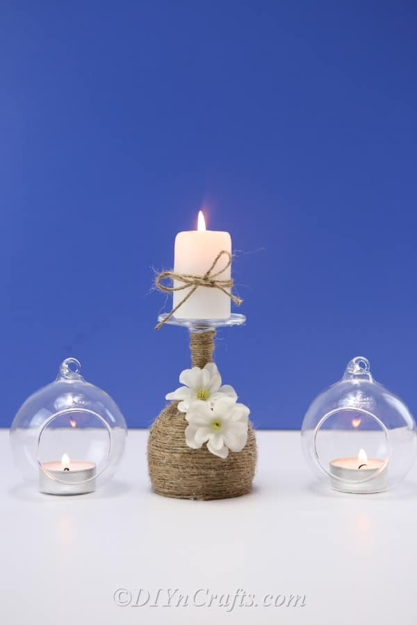 A rustic candle holder is displayed between two other decorative candle holders.