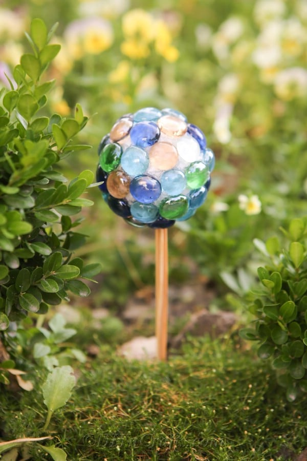 A DIY ball ornament stands among plants.