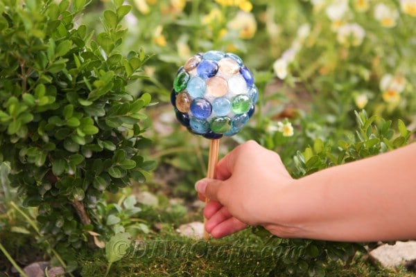 A hand holding a small gazing ball surrounded by plants.