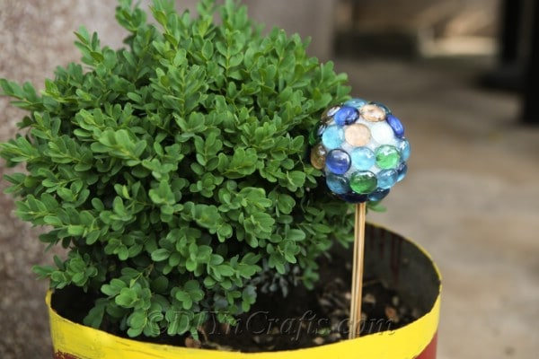 A DIY lawn ball ornament in a planter.