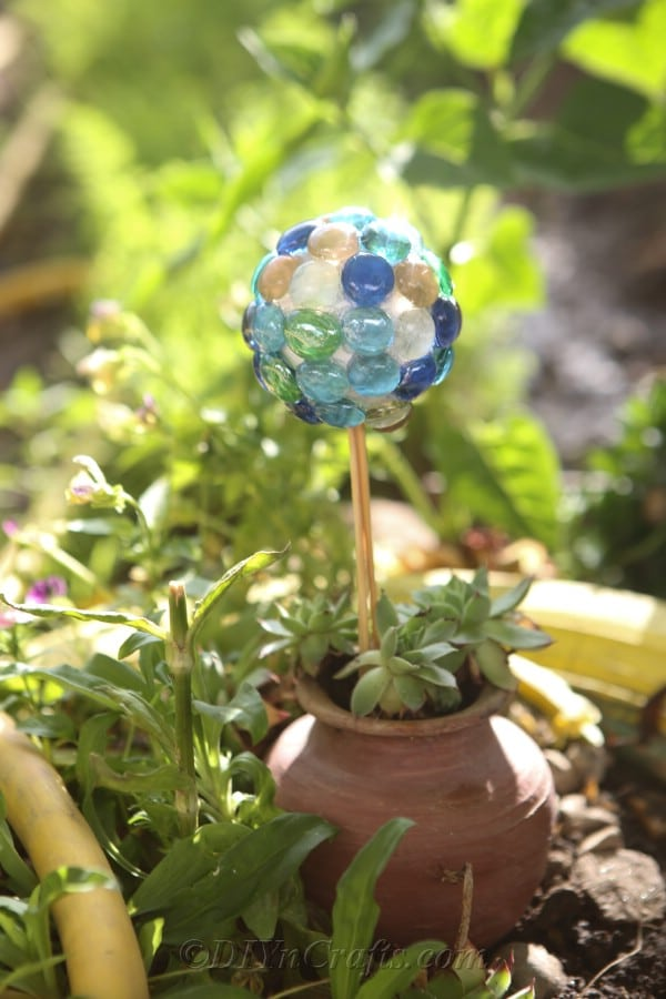 A DIY lawn ball next to a planter.