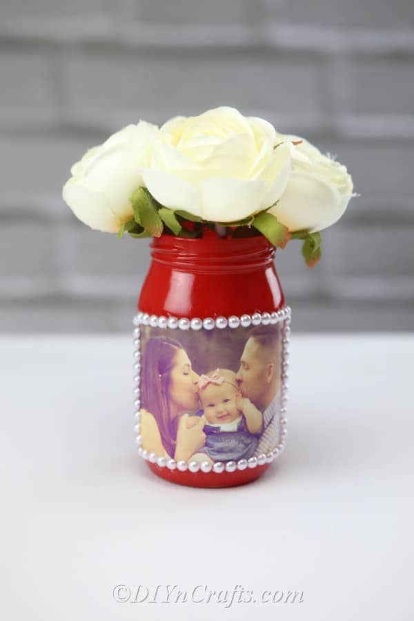 Flowers in a DIY jar vase displaying a photograph.