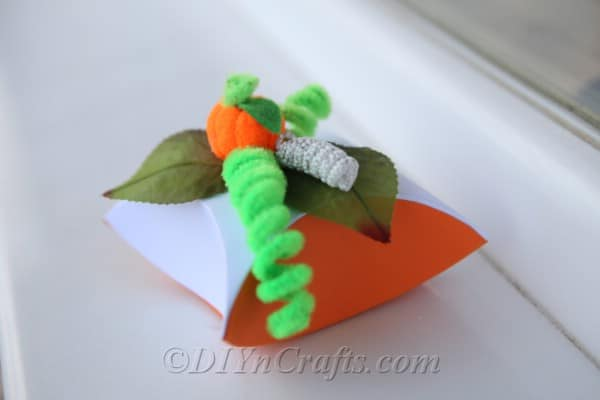 A diy gift box pumpkin sitting on a white windowsill
