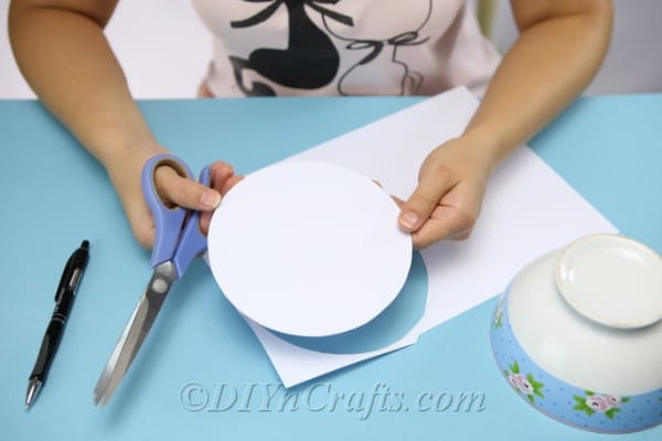 Cutting the circles out of the cardstock to create a diy gift box