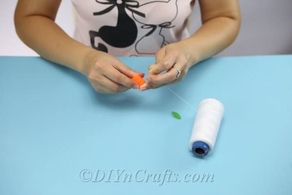 Wrapping a pom pom with thread to create a pumpkin for adding to the top of a diy gift box