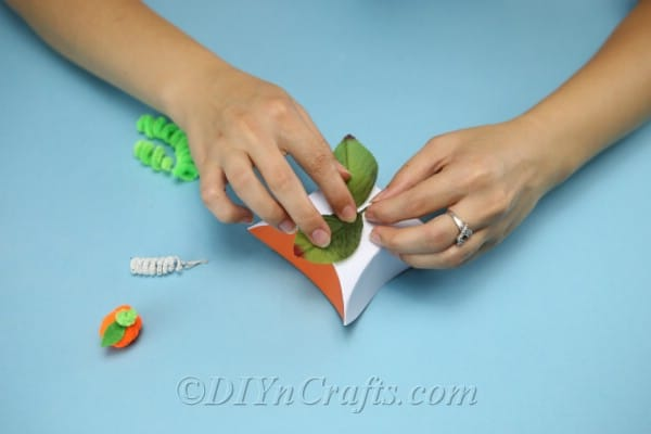 Gluing artificial leaves to the top of cardstock box to create a diy gift box