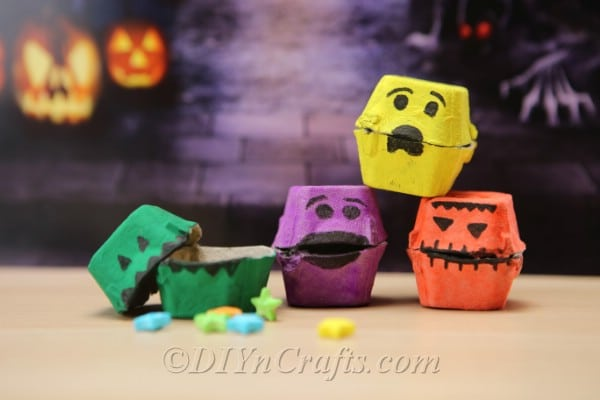 A stack of Halloween monster treat boxes sitting in front of a purple halloween themed banner