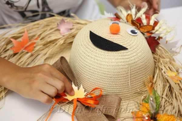 Adding the final decorations to your harvest decor scarecrow