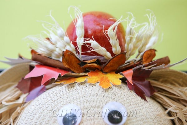 Finished lady scarecrow harvest decor with an apple on top as a hat