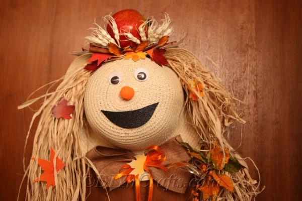A harvest decor lady scarecrow hanging on a wooden door
