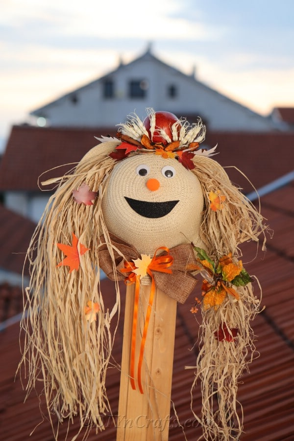 Harvest decor scarecrow outside in front of buildings