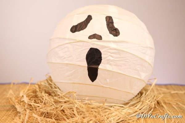 A surprised face ghost paper lanterns craft sitting on a stack of decorative straw