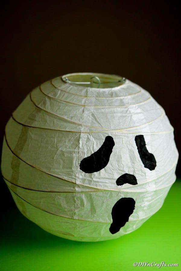 ghost paper lantern on green table in dark
