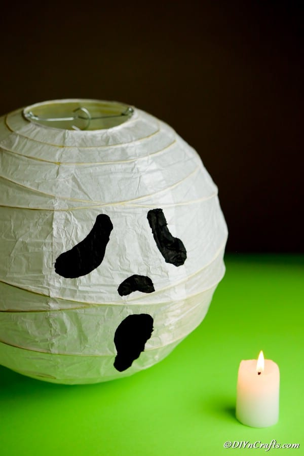 A ghost paper lantern sitting on a green surface next to a candle