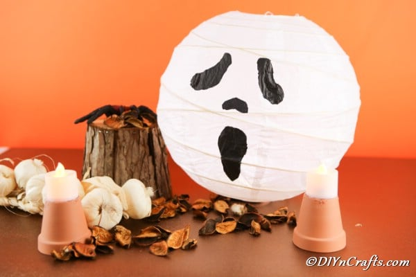 Ghost lantern sitting on a brown table with fall decorations around it