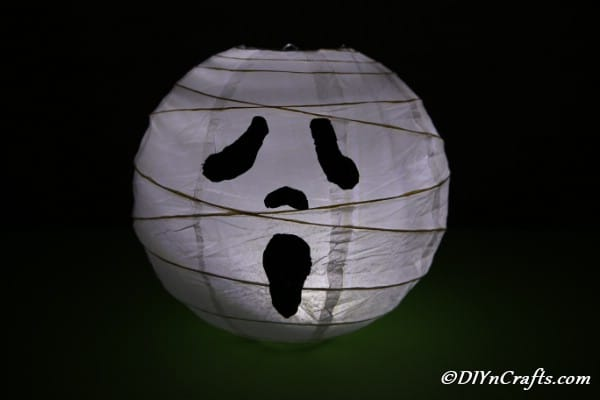 Ghost paper lanterns sitting in a dark room with candle lit