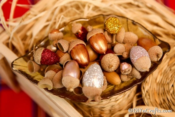 A fall basket filled with glitter acorns