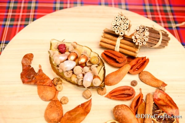 A table displayed with fall elements including glitter acorns for harvest decor