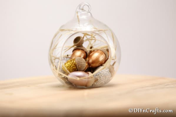 Glitter acorn decoration as a harvest decor in a glass globe