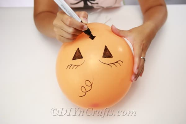Drawing the face on halloween balloons for decorations
