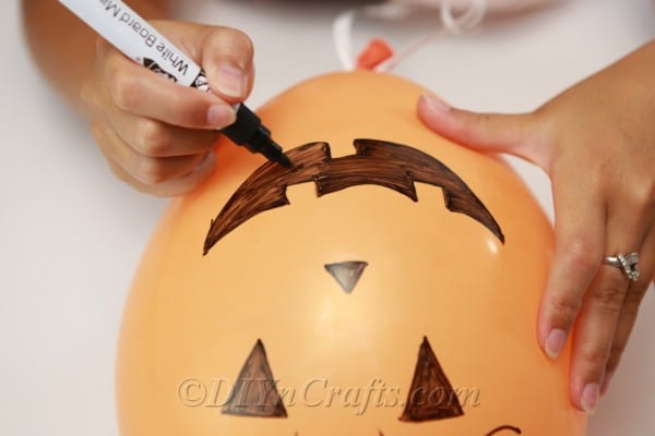 Drawing the mouth onto an orange jack o lantern halloween balloons design