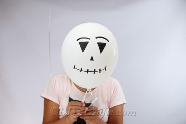 A jack skellington halloween balloons design being held by a woman