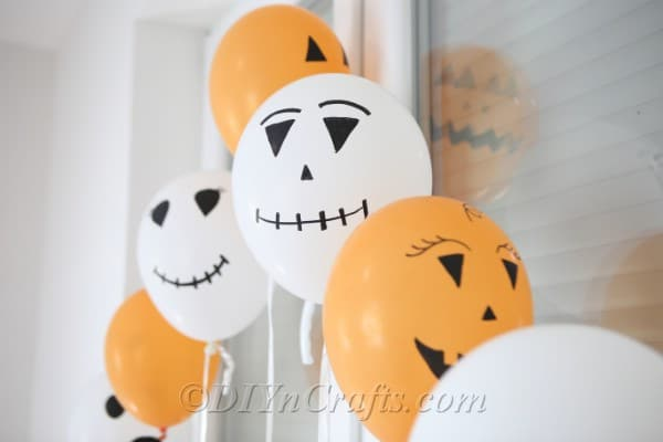 Finished halloween balloons hanging in front of a window
