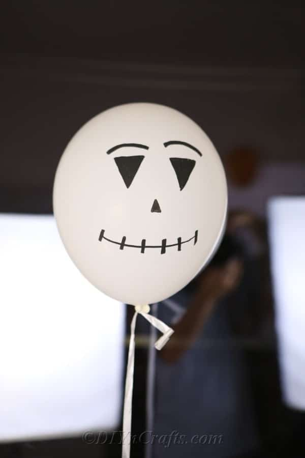 A white scarecrow or ghost halloween balloons design against a window