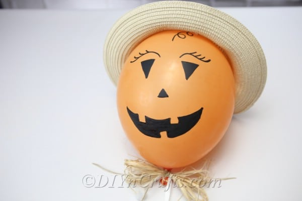 Scarecrow halloween balloons design with hat laying on a table