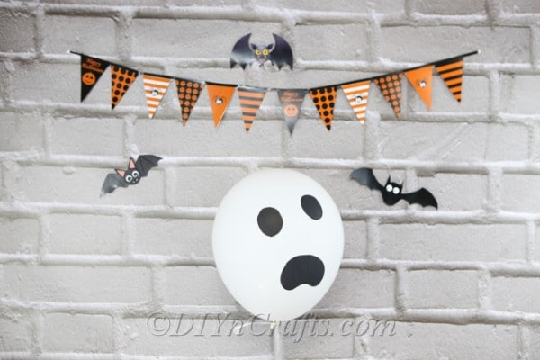 A ghost face halloween balloons decoration against gray brick wall with halloween banner above