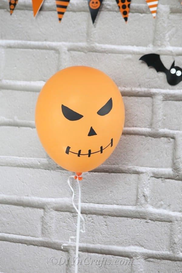 An orange jack o lantern halloweeen balloons hanging against a brick wall