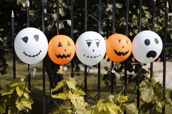 A row of halloween balloons tied to a black fenceline outside