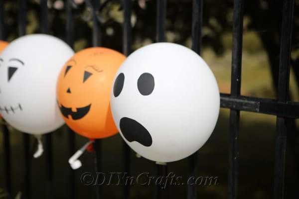 A picture of halloween balloons tied to a black metal fence
