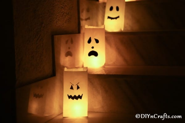 Halloween ghost luminary bags showcased on stairs in the dark