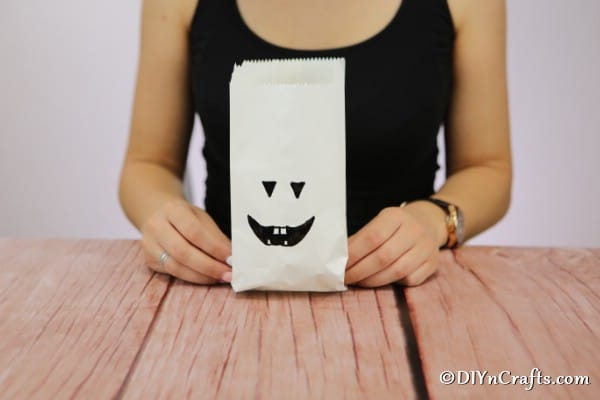 A woman holding a completed luminary bag with ghost face