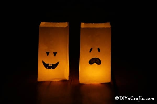 Two luminary bags decorated as ghosts sitting in a darkened area