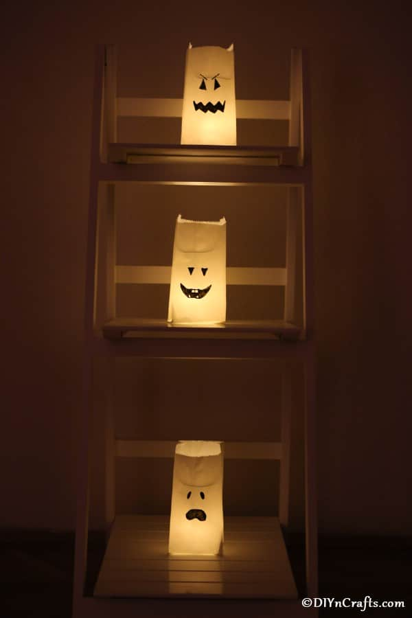 Halloween ghost faces luminary bags stacked on a shelf in a dark room
