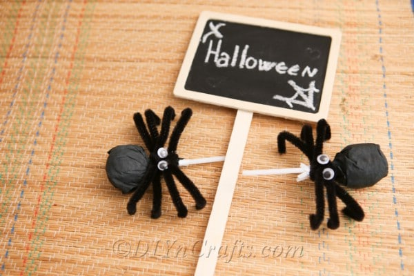 Two spider craft lollipops on a table with a small Halloween sign between them