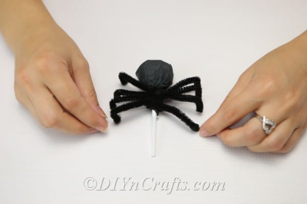 Spider legs secured to the spider craft Halloween lollipop